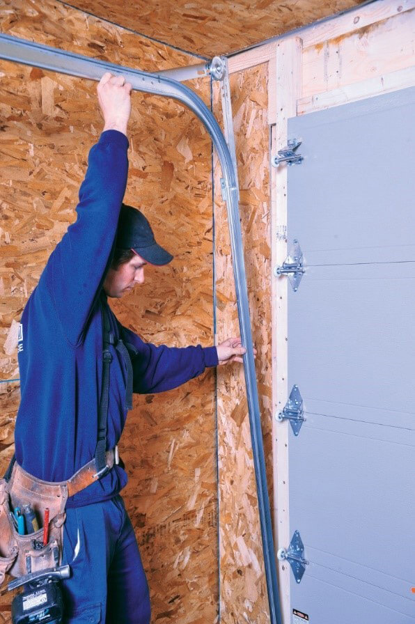 Installer installing garage door tracks
