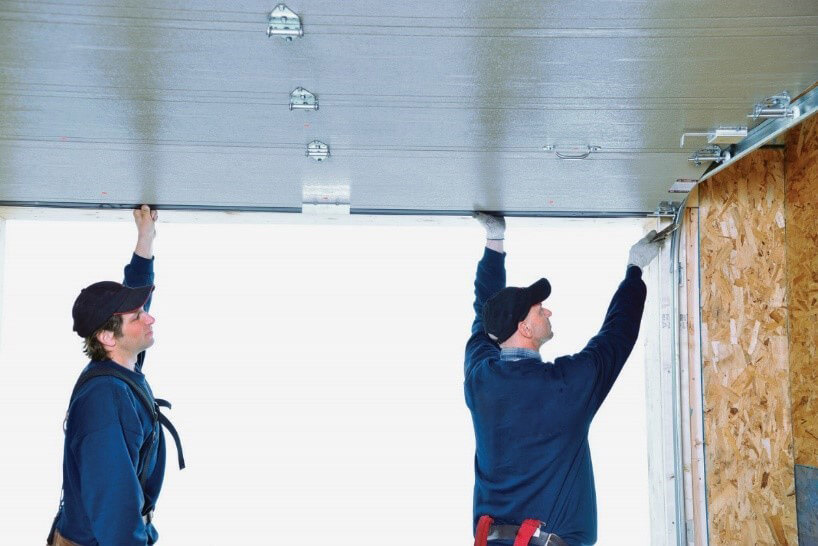 Two installers installing a garage door