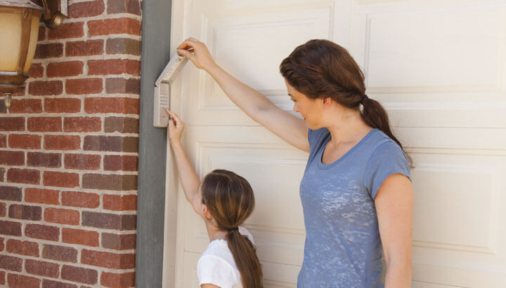 A mom and her daughter are going to the house from the garage. We can see that the garage door has secure door lock.