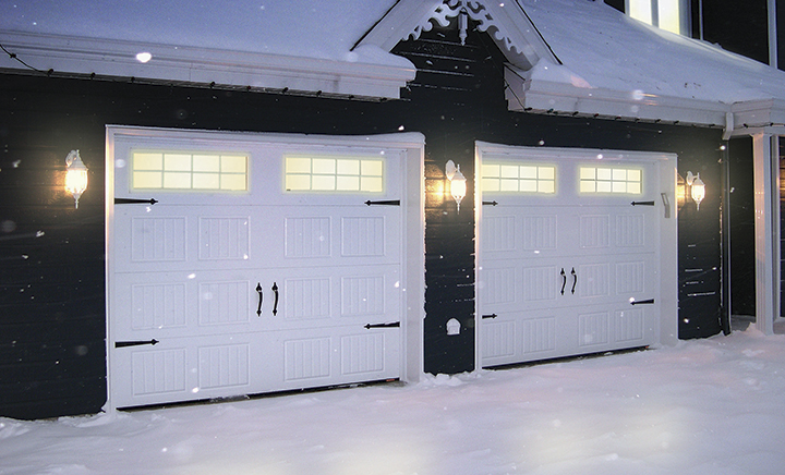 Traditional style blue house in winter, with double garage having 9' x 7' Standard+ North Hatley SP Ice White garage doors.