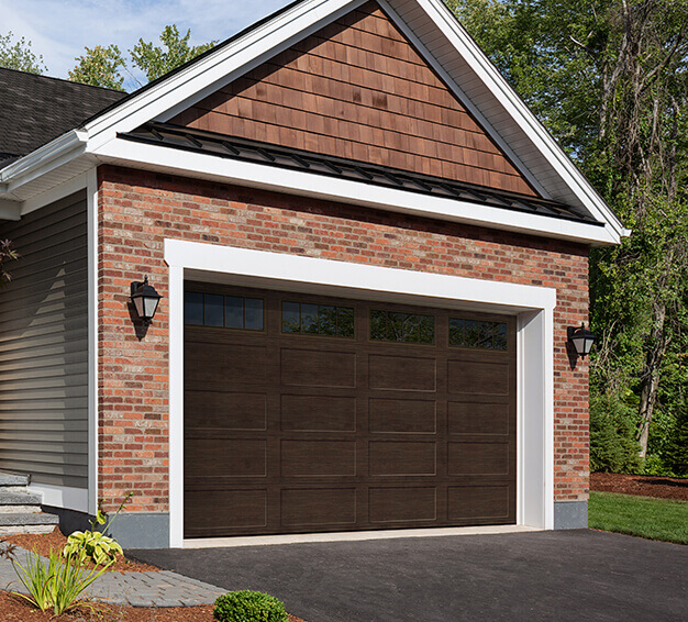 Simple Traditional Style garage doors with the Regal Shaker‑Flat Long design in the Dark Walnut color